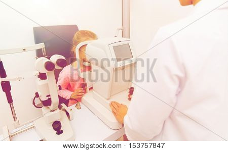 health care, medicine, people, eyesight and technology concept - optometrist with autorefractor checking patient vision eye clinic or optics store