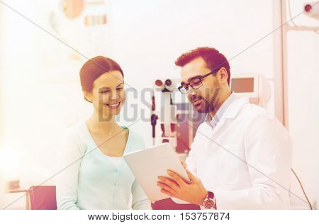 health care, medicine, people, eyesight and technology concept - optician in glasses with tablet pc computer and patient at eye clinic or optics store