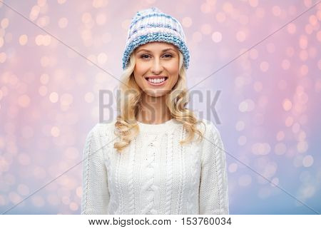 winter, fashion, christmas and people concept - smiling young woman in winter hat, sweater and gloves over rose quartz and serenity lights background