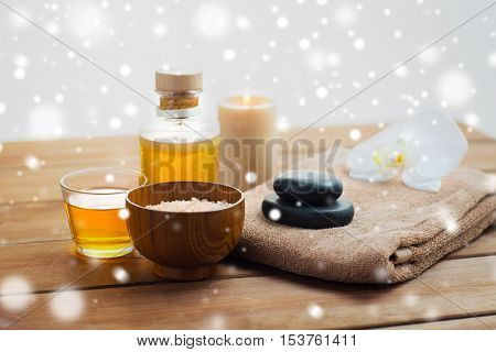 beauty, spa, bodycare, natural cosmetics and concept - himalayan pink salt with massage oil and bath towel on wooden table over snow