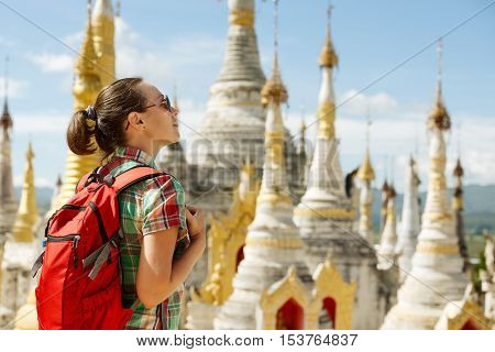 Hiker traveling with backpack and looks at Buddhist stupas. Myanmar (Birma)