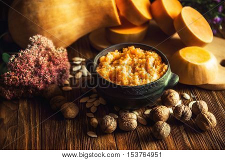 Porridge pumpkin in a clay bowl on wooden background. Pumpkin millet porridge with pumpkin in the background. Still life