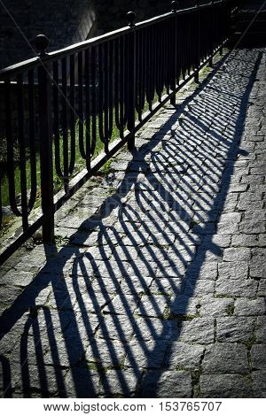abstract background iron railing shadow on stone pavement