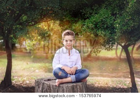 Boy 8 years old sitting on a tree stump on a sunny summer day. Kid outdoor enjoying nature. Handsome Boy barefoot sitting cross-legged.
