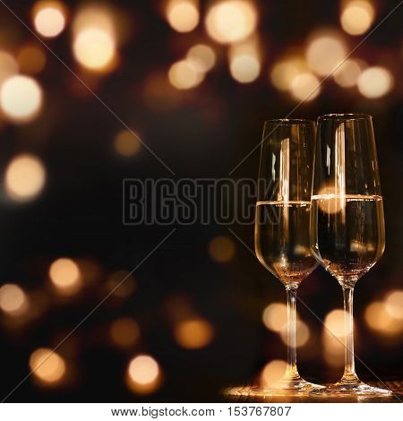 Two Champagne glasses for festive occasions in front of a dark background with golden lights and bokeh