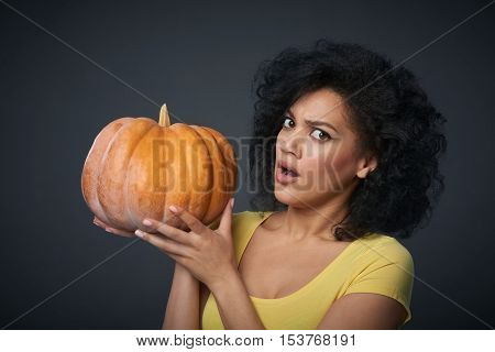 Sullen woman holding ripe pumpkin isolated over grey background