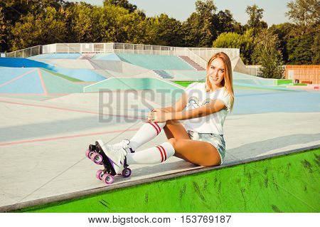 Beautiful blonde girl posing on a vintage roller skates in denim shorts and white T-shirt in the skate park on a warm summer evening. Rollers quads derby. Girl sitting on the edge of the ramp.