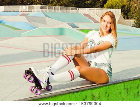 Beautiful blonde girl posing on a vintage roller skates in denim shorts and white T-shirt in the skate park on a warm summer evening. Rollers quads derby. Girl sitting on the edge of the ramp. Close up.