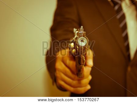 Asian businessman with gun pointing forward,vintage style