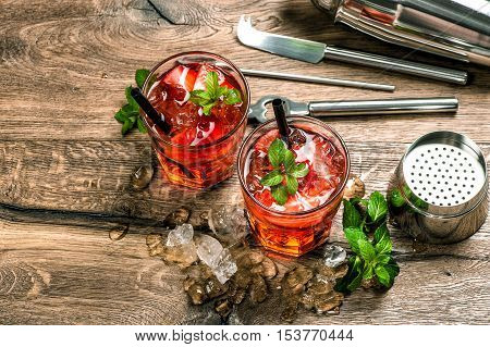 Red Cocktail with strawberry mint leaves ice. Drink making bar tools
