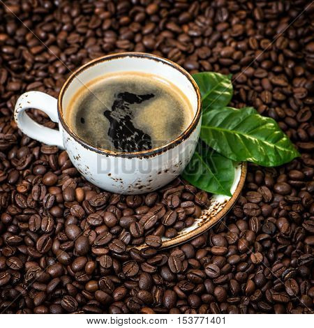Black coffee with green leaves on caffee beans background. Vintage style toned picture