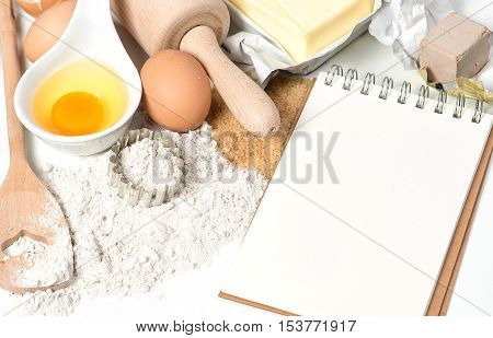 Food background. Recipe book and baking ingredients eggs flour sugar butter yeast.