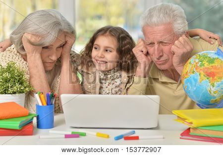Portrait of happy grandparents  and a little girl using laptop