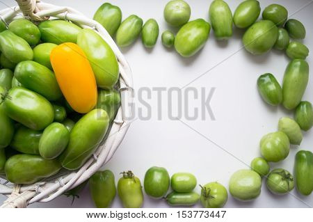 Young green tomatoes in a basket with place for text