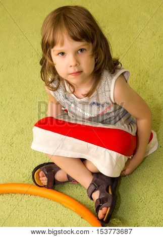 Beautiful little girl sitting on the floor in Montessori kindergarten . The girl folded her Turkish legs . She looks directly into the camera.