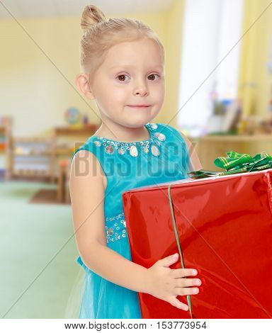 The concept of pre-school education of the child among their peers . on the background of the playroom with shelves for toys. Montessori.Caucasian little girl in a blue dress