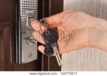 hand unlocking front door with key closeup