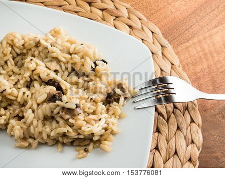 A white plate with an italian risotto with parasol mushroom and a fork