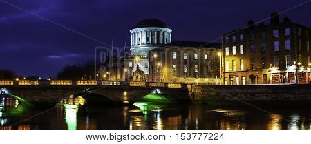 Illuminated Four Courts building in Dublin, Ireland at night. Reflection in Liffey river with bridge, various cafes, shops and restaurants