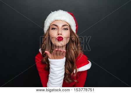 Santa's helper sends an air kiss over black background. Close-up