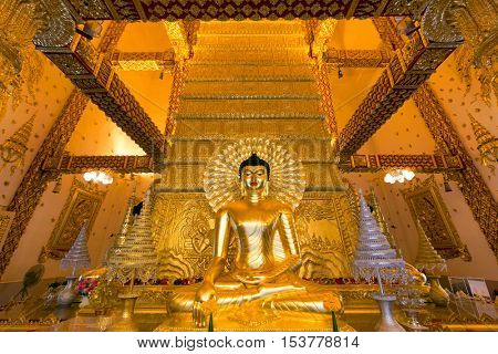 Golden Buddha statue inside the Wat Phrathat Nong Bua temple in Ubon Ratchathani, Thailand