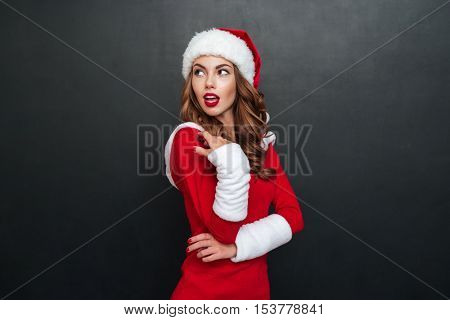 Woman in christmas costume posing standing sideways and holds a hand near the face