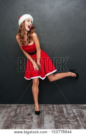 Girl with Santa hats standing on one leg. Santa's helper. Santa's dress.