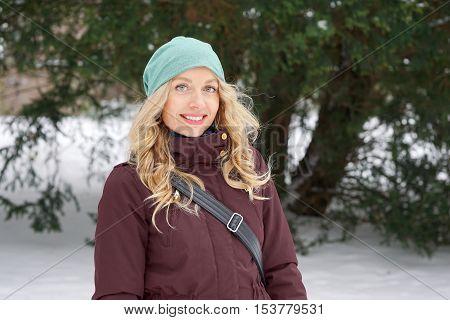 blond woman wearing warm winter fashion and woolen hat enjoying winter