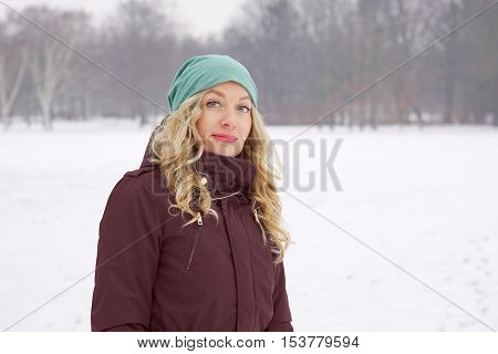 blond woman taking a walk in snow covered park in winter