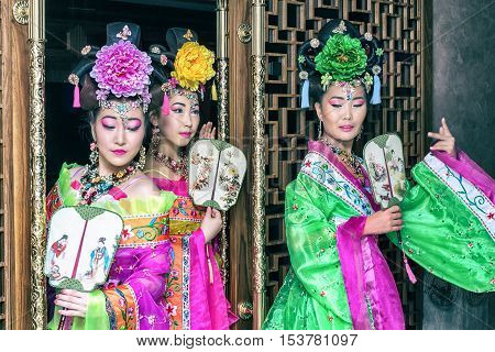 three beautiful geisha in traditional national dress with fan out of the door