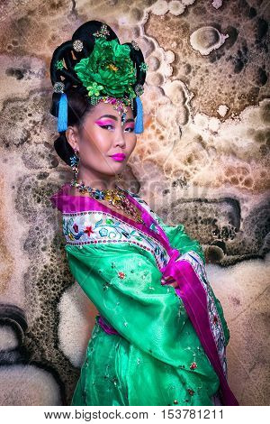 Beautiful Chinese Woman In A Rich Green Traditional Chinese Dress Against Marble Wall