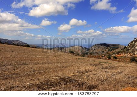 A stubble field near Moundros high in the mountains of central Crete, Greece, with spectacular views north to the cliffs of the Drapano peninsula, the sea and distant Akrotiri.