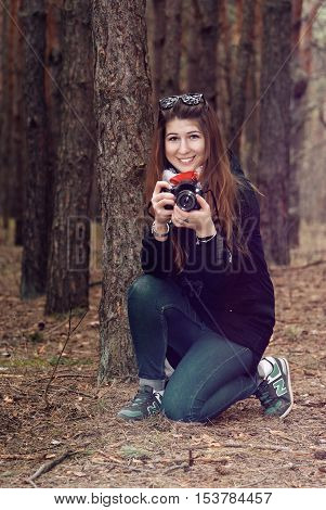 Young girl photographer on autumn walk in the woods