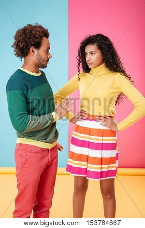 Beautiful african american young couple standing and arguing over colorful background