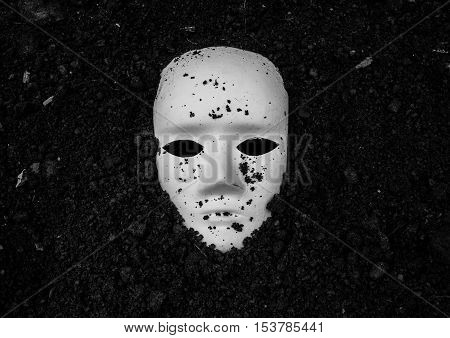 White mask in soil,Horror background for Halloween concept and book cover ideas