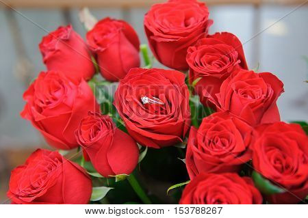 Wedding ring on the rose-bud. Diamond ring over the red rose bud. Bouquet of bright red roses.