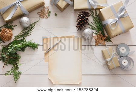 Winter holidays background. Gift wrapping and decorating christmas present, boxes in craft paper with satin silver ribbon. Top view of white wooden table with copy space on sheet of paper