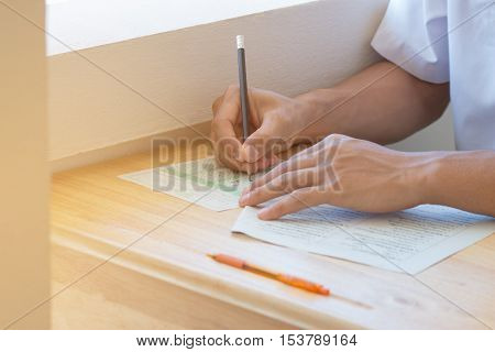 student testing in exercise exams answer sheets or test paper with pencil : education concept