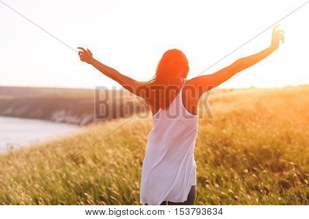 Teenage girl enjoy with sunshine in field. Morning back view of young woman at sunrise. Freedom concept with sunlight filter effect
