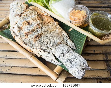 Grilled fish with salt in bamboo basket.