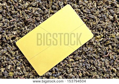 Oolong tea background and blank golden color card for text, copyspace.