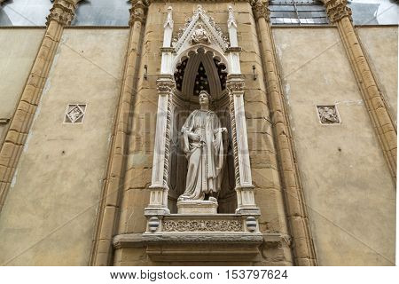 FLORENCE, ITALY - SEPTEMBER 2016: Marble statue of Saint Philip, Guild of Shoemakers by Nanni di Banco, Orsanmichele church with 1 of 14 external niche figures in Florence, Italy on September 21, 2016