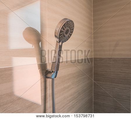 Head shower on tile wall decorate of bathroom.