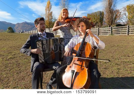 Portrait of three young musicians, scene at a farm