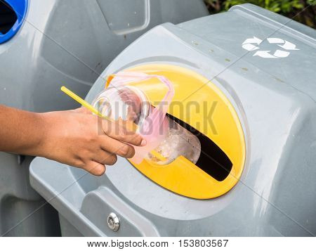 Hand throws away waste material into trash container.