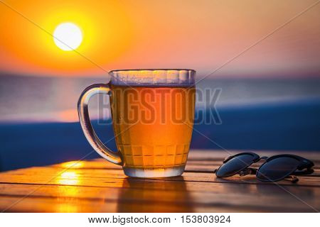 Cold Draught Beer with bokeh of the sunset in the sea background