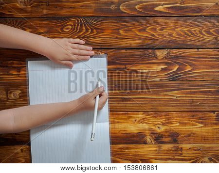 Cute little boy writes in notebook sitting at desk