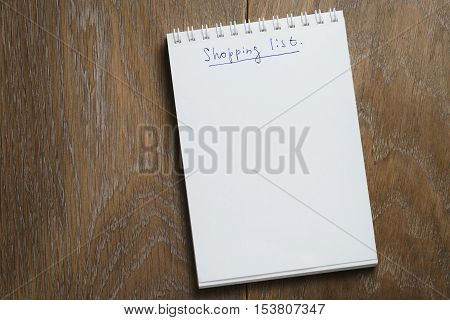 shopping list on notepad on wood table, blank notepad for your text