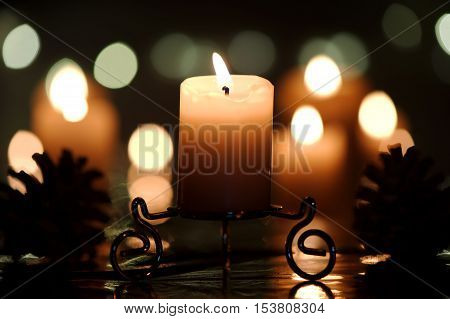 Burning candle on a stand with shapes of cones