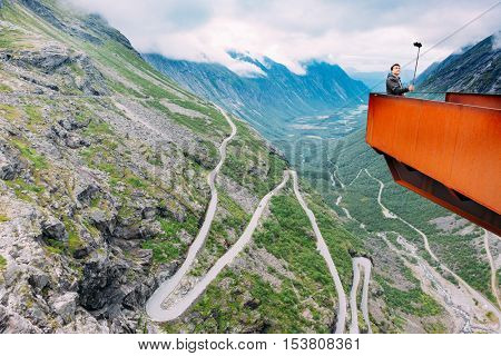 TROLLSTIGEN, NORWAY - AUGUST 5, 2016: caucasian tourist takes a selfie using a selfiestick on a panoramic terrace in front of Trollstige, a famous norvegian mountain road. Trollstigen, Norway, Europe.